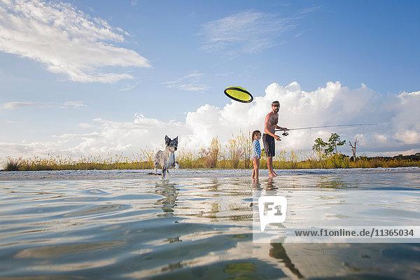 Vater und Tochter fischen und werfen fliegende Scheibe für Hund  Fort Walton Beach  Florida  USA