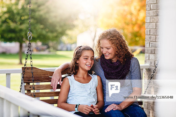 Aunt and niece sitting on porch swing  smiling