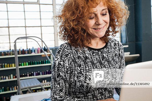 Mature female fashion designer typing on laptop in workshop
