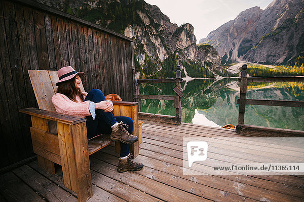 Woman relaxing on wooden chair  Lago di Braies  Dolomite Alps  Val di Braies  South Tyrol  Italy