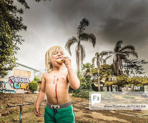 Junge isst Leckerli mit Marmelade  die auf die Brust tropft