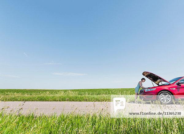 Frau schaut unter die Motorhaube eines kaputten Autos