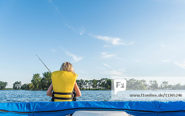 Rear view of boy wearing life jacket fishing