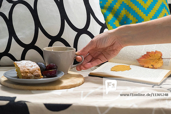 Hand of woman with cup of coffee and cake on sofa