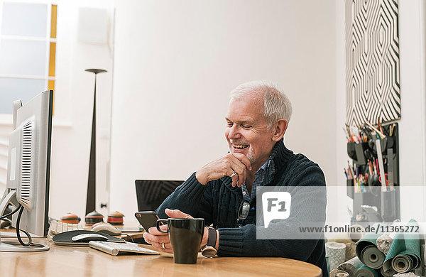Senior man smiling  using mobile phone at work desk