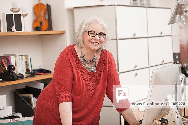 Frau lächelt am Arbeitstisch