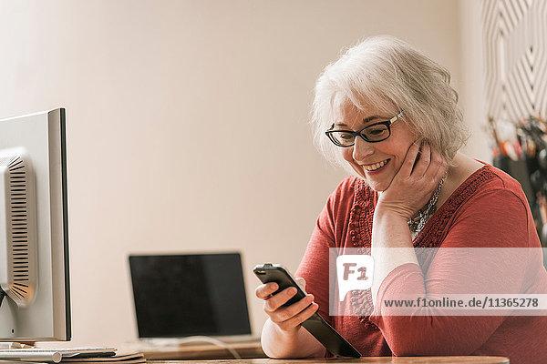 Lächelnde Frau  die ein Mobiltelefon am Schreibtisch benutzt