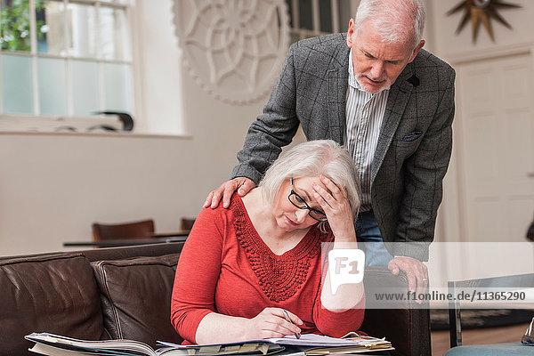 Älterer Mann tröstet Frau auf Couch
