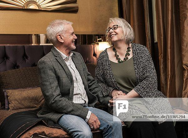 Älteres Ehepaar lächelt und unterhält sich im Bett