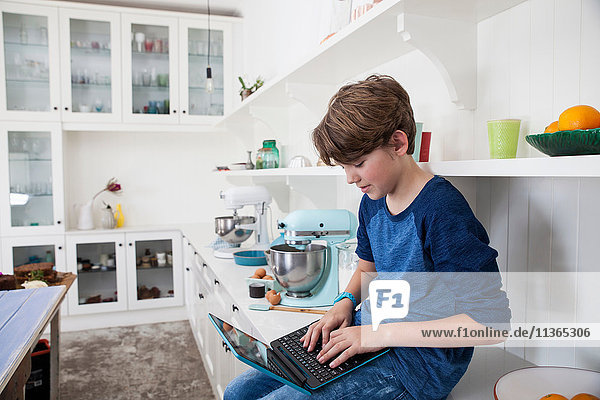Boy sitting on kitchen work surface  using laptop computer
