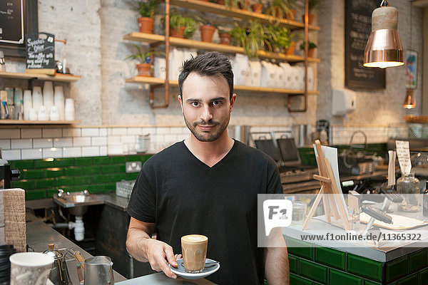Portrait of young male barista serving glass of coffee in cafe