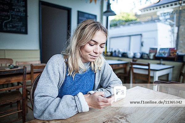 Junge Frau im Cafe sitzend  mit Smartphone  lächelnd