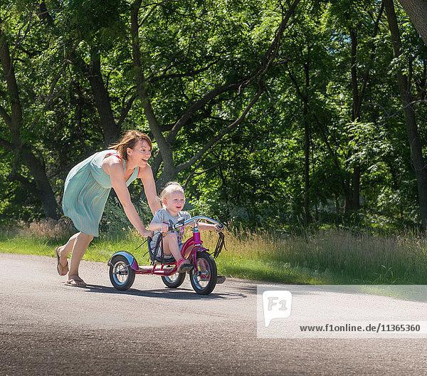 Mutter schiebt Tochter auf Dreirad