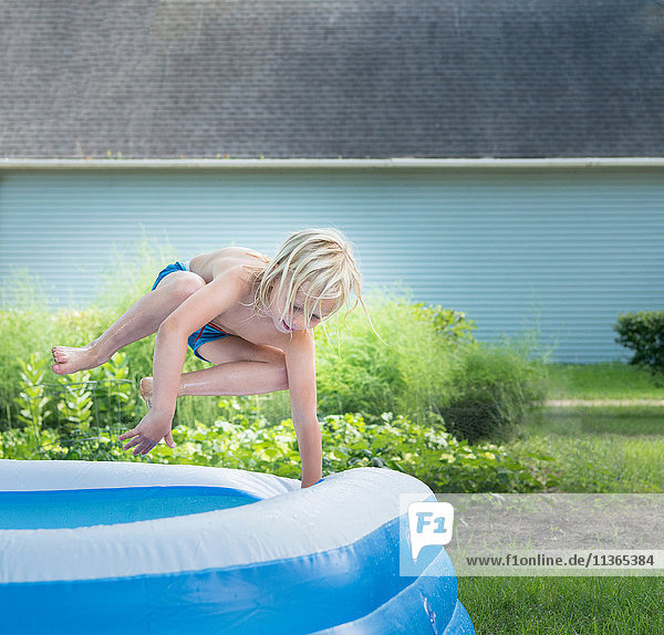 Boy jumping into paddling pool