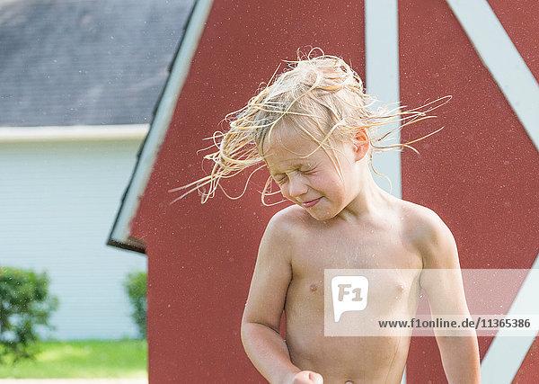 Junge schüttelt nasses Haar
