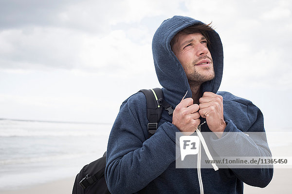 Young man wearing hoody on beach  Western Cape  South Africa