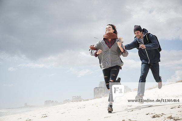 Junges Paar rennt und jagt am Strand  Western Cape  Südafrika