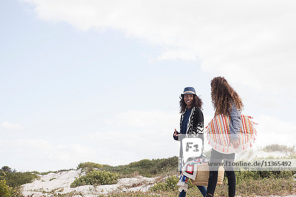 Two young female friends strolling on beach  Western Cape  South Africa