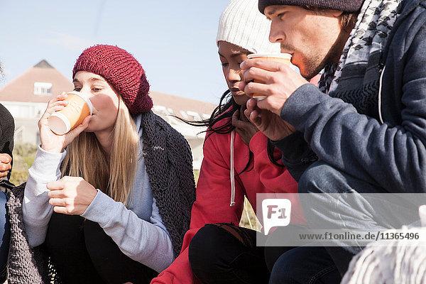 Junge erwachsene Freunde kauern am Strand und trinken Kaffee zum Mitnehmen  Western Cape  Südafrika