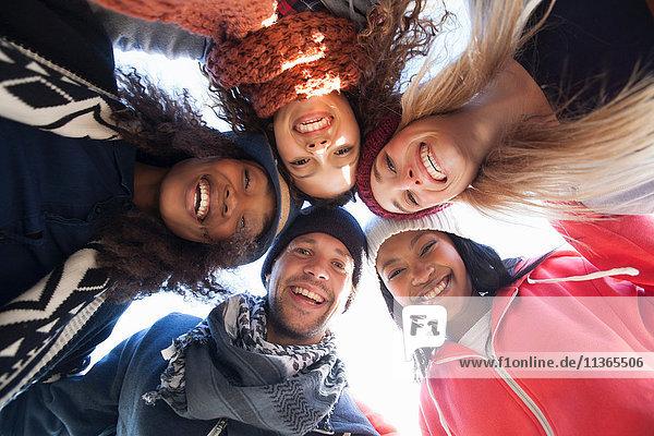 Niedrigwinkel-Porträt von fünf glücklichen erwachsenen Freunden  die sich in einem Kreis kauern