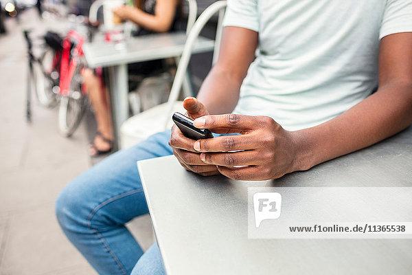 Schnappschuss eines jungen Mannes  der auf einem Smartphone im Stadtcafé simst.