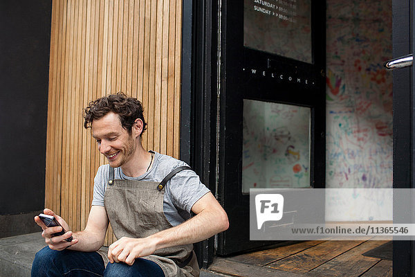 Kellner macht eine Pause auf Cafe Schritt Blick auf Smartphone