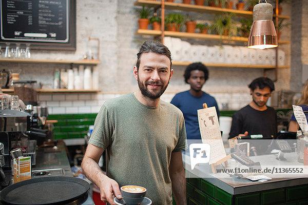 Porträt eines männlichen Barista  der Kaffee im Café serviert.