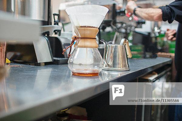 Ausschnitt eines männlichen Barista  der Kaffee im Cafe zubereitet.