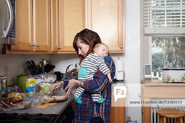 Mutter hält schlafenden Jungen und bereitet Sandwich zu