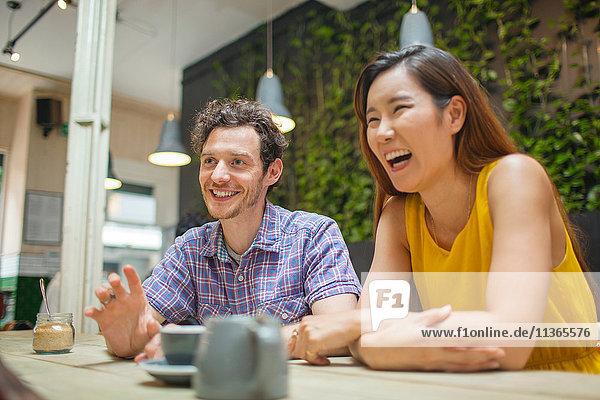 Mittleres erwachsenes Paar  das am Kaffeetisch redet