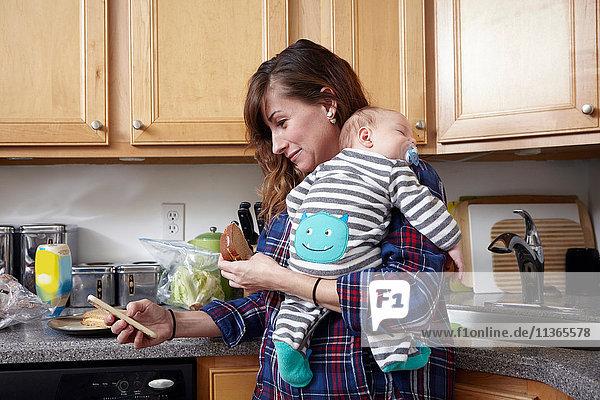 Mutter hält schlafendes Baby Junge und schaut auf Smartphone