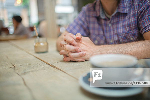 Ausgeschnittene Aufnahme eines Mannes am Coffee-Shop-Tisch