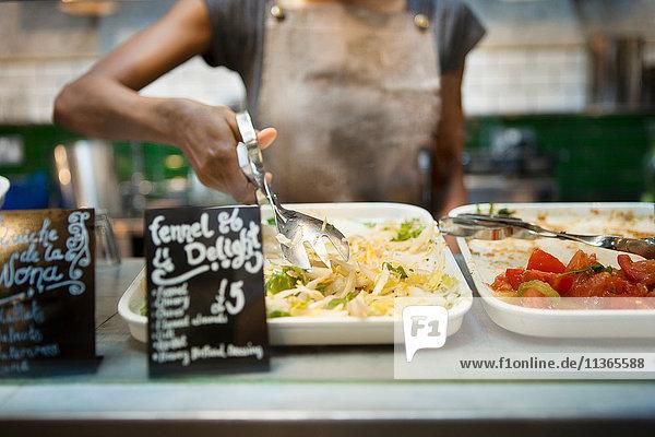 Mittelteil der Kellnerin  die Salat aus der Vitrine des Cafés serviert