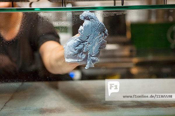 Frauenhand reinigt Vitrinenglas im Café