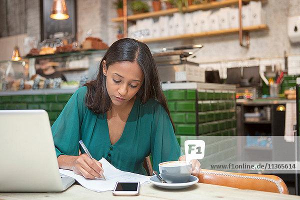 Mittlere erwachsene Frau beim Papierkram am Kaffeetisch