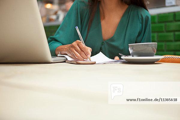 Abgeschnittene Aufnahme einer Frau  die Papierkram am Kaffeetisch erledigt.