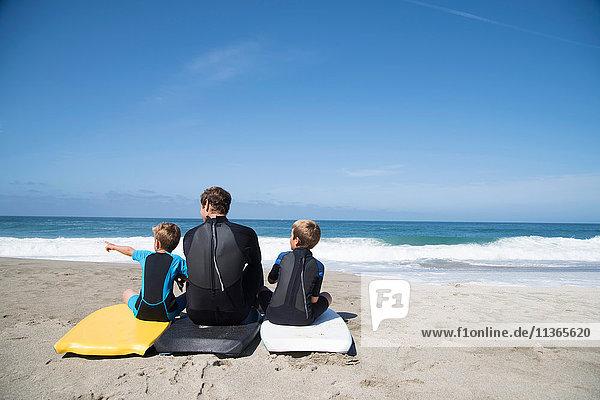 Rückansicht eines Mannes und zweier Söhne  die auf Bodyboards sitzen und nach vorne zeigen  Laguna Beach  Kalifornien  USA