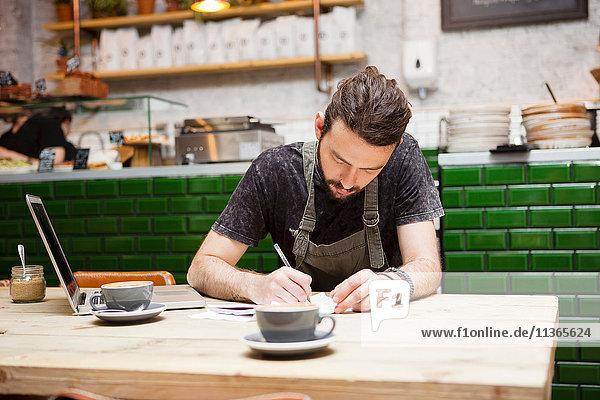 Junge männliche Kaffeehausbesitzerin bei Tisch