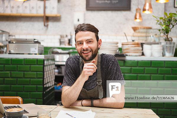 Porträt eines männlichen Cafébesitzers  der Papierkram am Tisch erledigt