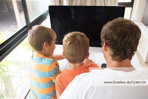 Rückansicht von Mann und zwei Söhnen mit Desktop-Computer