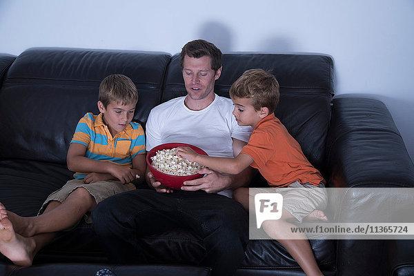 Mann und zwei Söhne essen Popcorn auf dem Sofa