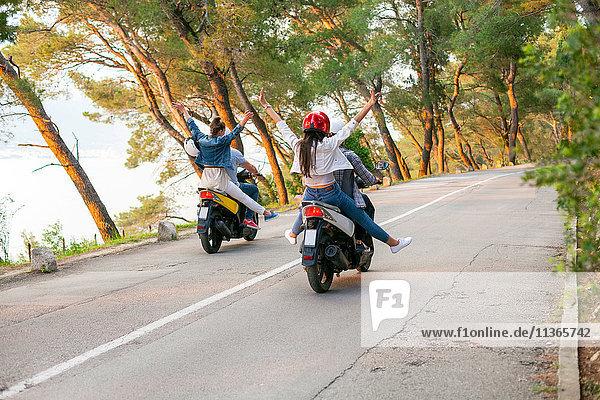 Rückansicht von zwei Moped fahrenden Paaren auf einer Landstraße  Split  Dalmatien  Kroatien