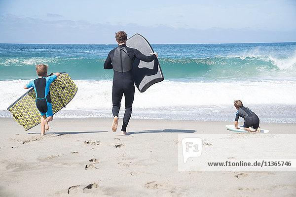 Rückansicht von Vater und zwei Söhnen  die mit Bodyboards am Strand laufen  Laguna Beach  Kalifornien  USA