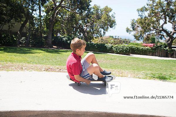 Boy in park skateboarding sitting down