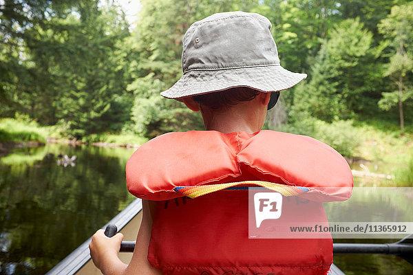 Junge im Kanu  Rückansicht