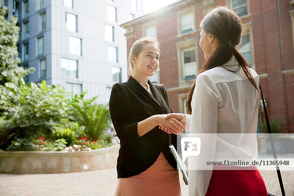 Businesswomen shaking hands at meeting  London