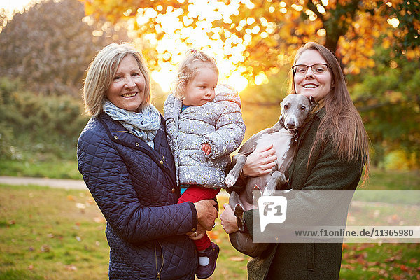 Portrait of senior woman with daughter  granddaughter and dog in autumn park