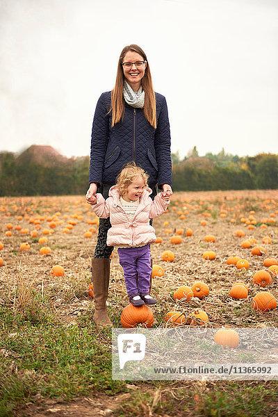 Porträt einer mittelgroßen erwachsenen Frau und einer Kleinkind-Tochter auf einem Kürbis im Feld stehend