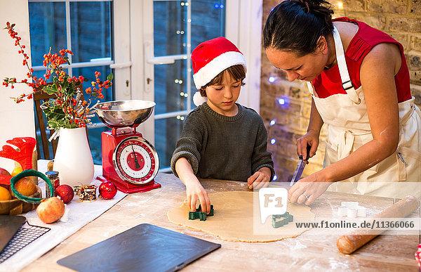 Reife Frau bereitet mit Sohn Weihnachtsplätzchen an der Küchentheke zu