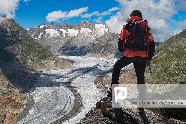 Rear view of lone male climber looking out over Aletsch Glacier  Canton Wallis  Switzerland